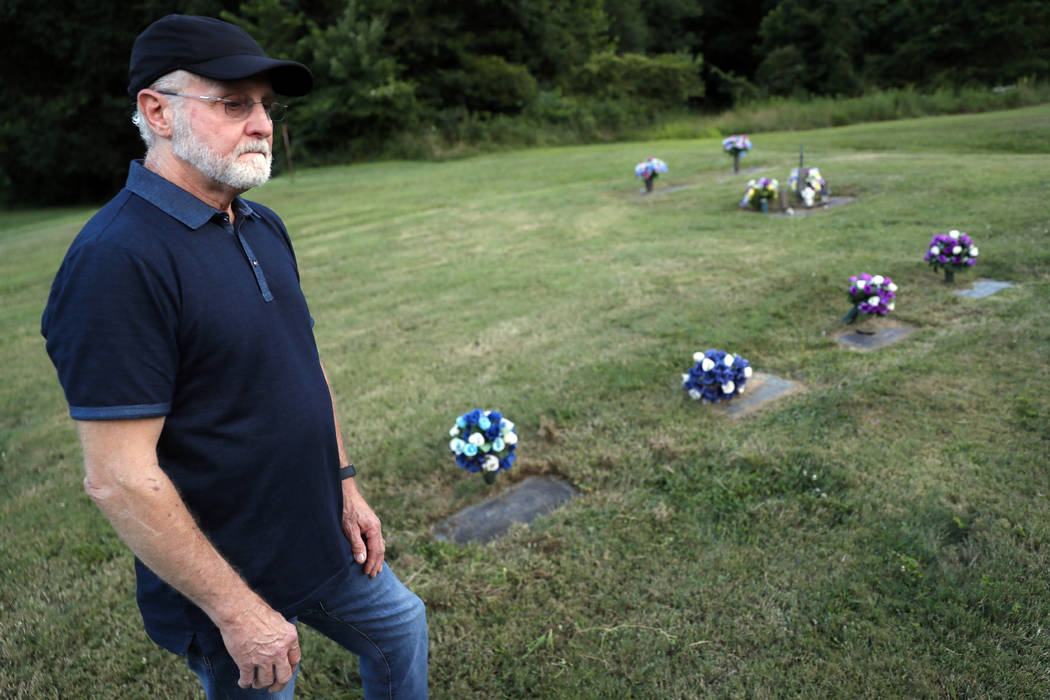 Eddie Davis stands beside the gravestone of his son Jeremy, furtherest left, who died from the ...