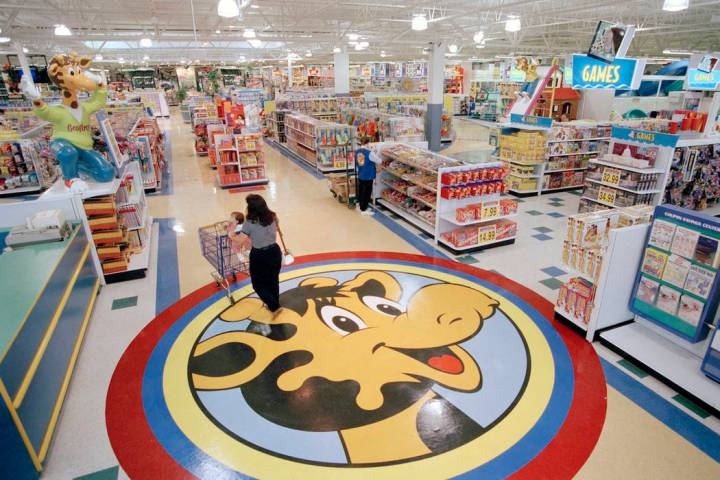 In this July 30, 1996, file photo, a woman pushes a shopping cart over a graphic of Toys R Us m ...