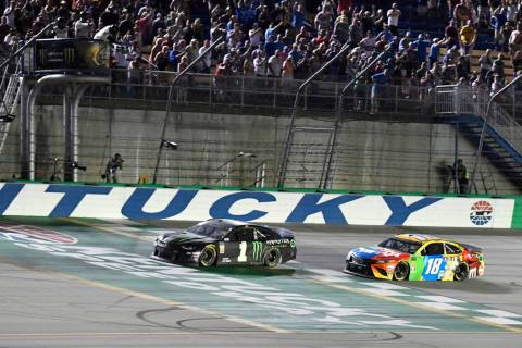 Kurt Busch crosses the finish line ahead of Kyle Busch (18) to win the NASCAR Cup Series auto r ...