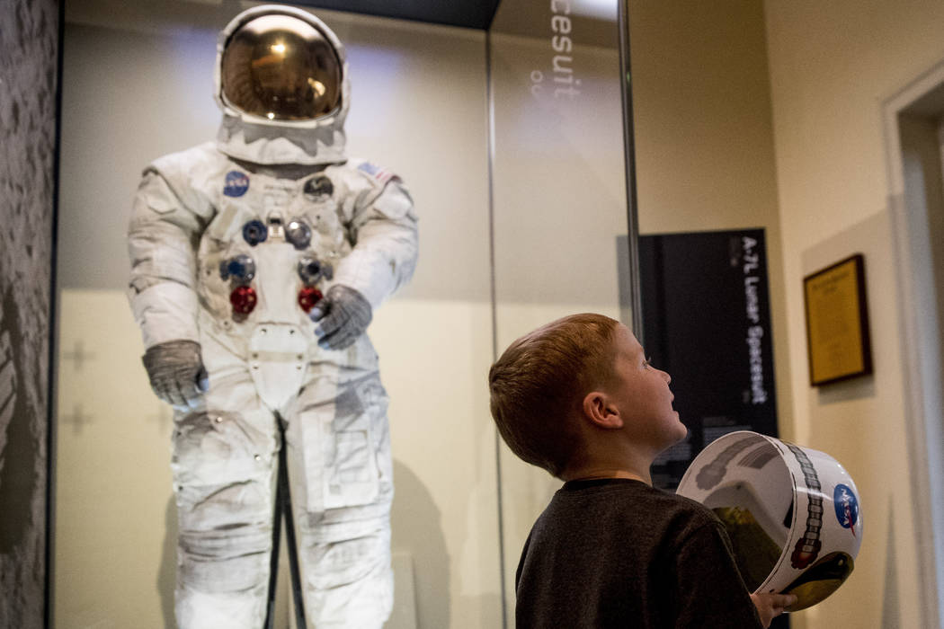 Jack Heely, 5, of Alexandria, Va., plays with a toy space helmet as he arrives as one of the fi ...