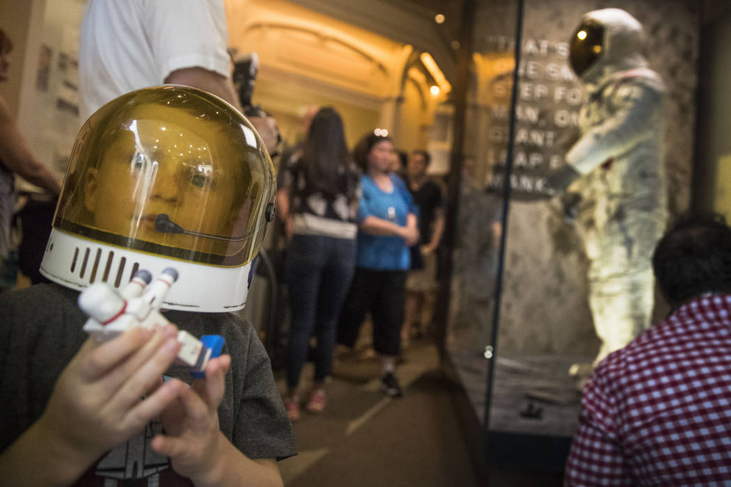 Jack Heely, 5, of Alexandria, Va., wears a toy space helmet as he arrives as one of the first v ...