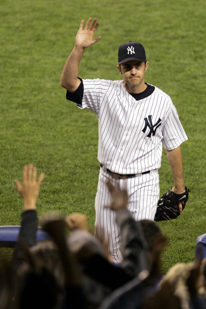 New York Yankees pitcher Mike Mussina waves to the crowd while leaving the game during the seve ...