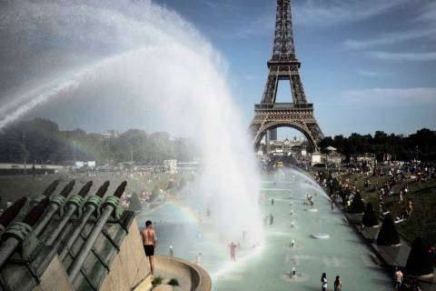 People cool off in the fountains of the Trocadero gardens, in front of the Eiffel Tower, in Par ...