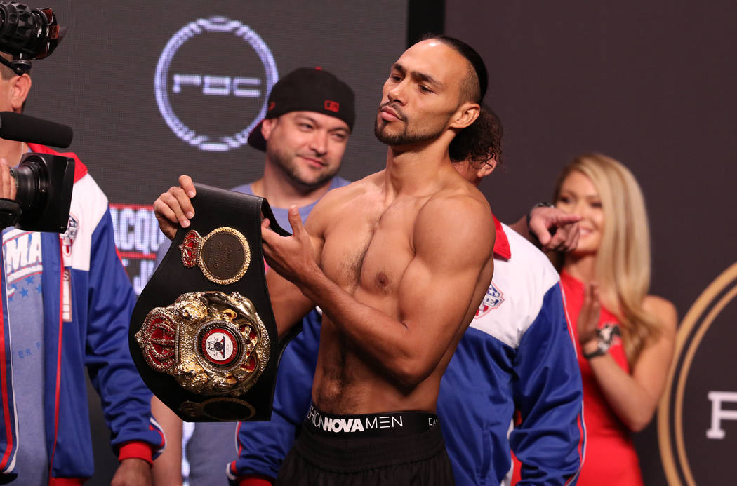 Keith Thurman picks up his championship belt during the official weigh-in at the MGM Grand Gard ...