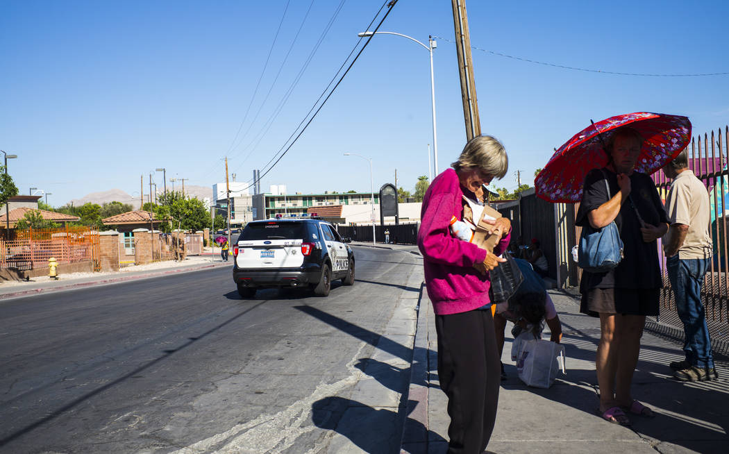 A Las Vegas police car passes by homeless people on Foremaster Lane near downtown Las Vegas on ...
