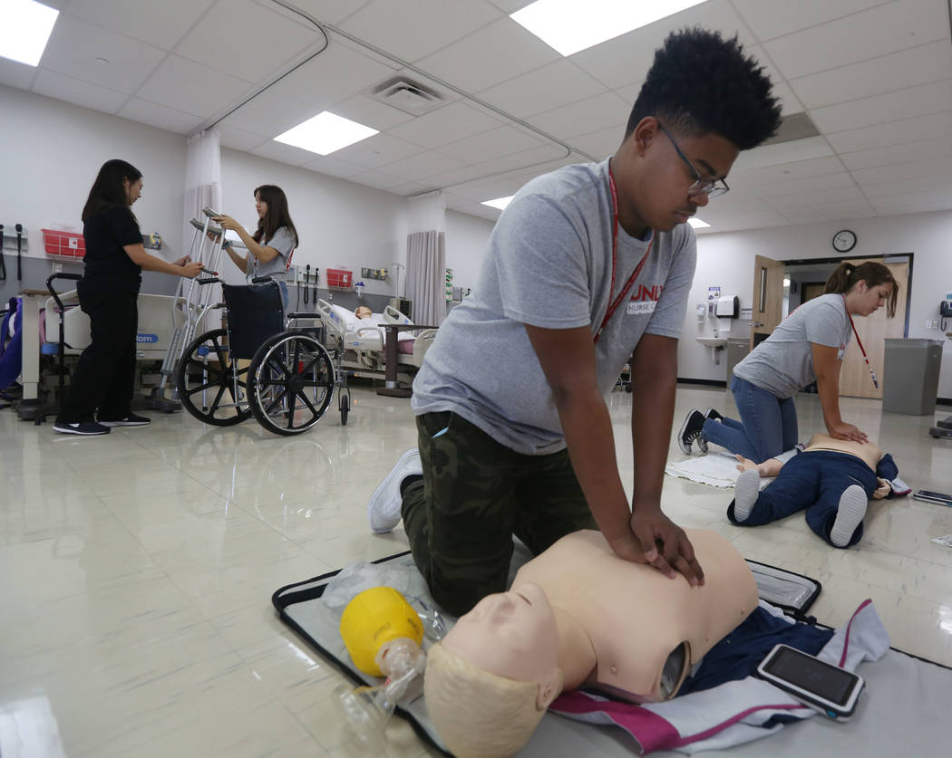 James Treadwell, 15, left, and Lea Jensen, 17, right, practice breathing on a medical doll at C ...