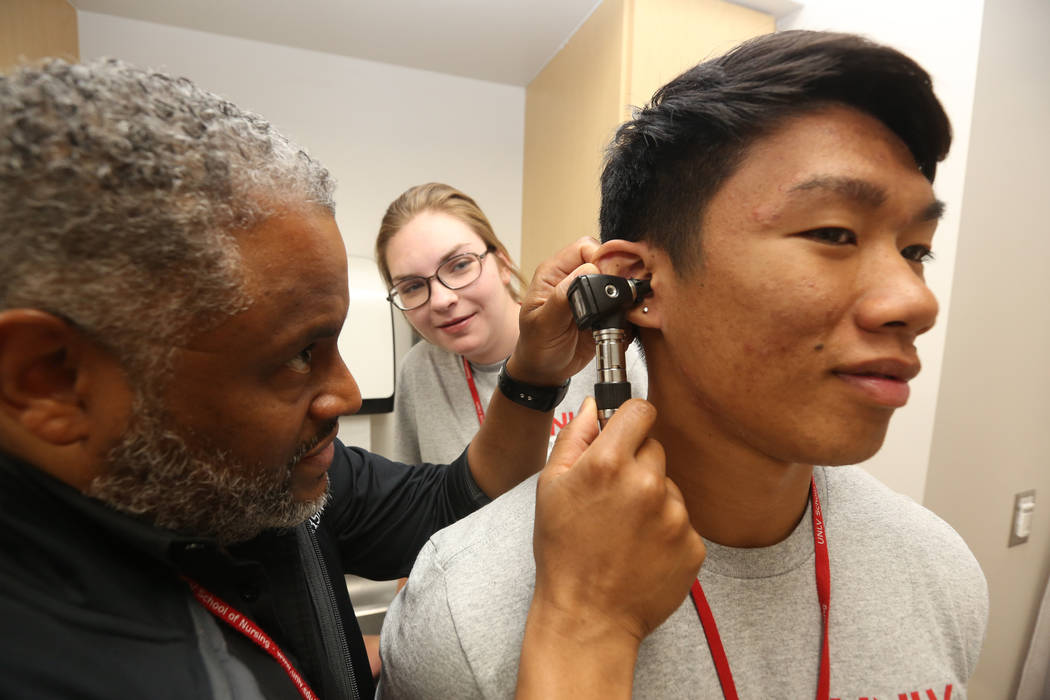 Dr. Aaron Bellow Jr., 45, checks the ears of student John Patriarca, 18, right, as Anabelle C ...