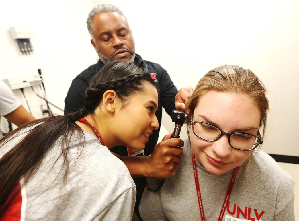 Dr. Aaron Bellow Jr., 45, checks the ear of Anabelle Carino, 17, right, as Victoria Tarango, 1 ...