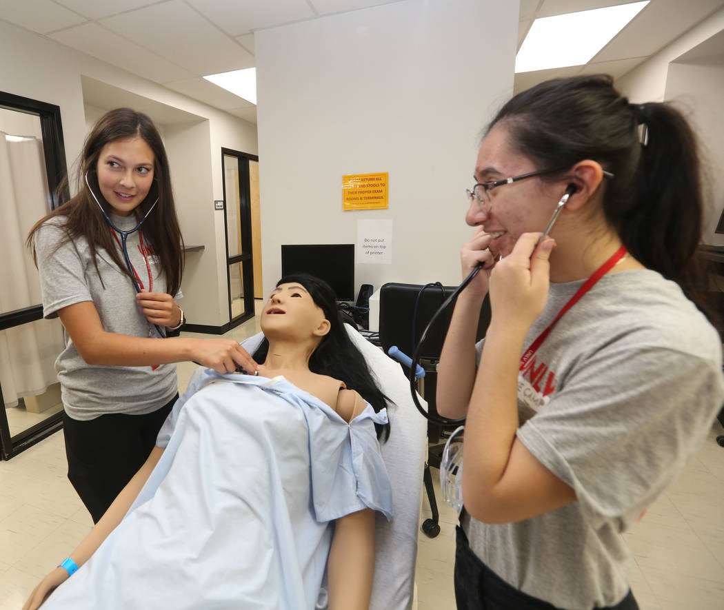 Students Vanessa Panfil, 17, left, and Dulce Hernandez, 18, right, practice breathing on a medi ...