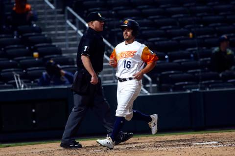 Las Vegas Aviators left fielder Mark Payton (16) scores a run against the Sacramento River Cats ...