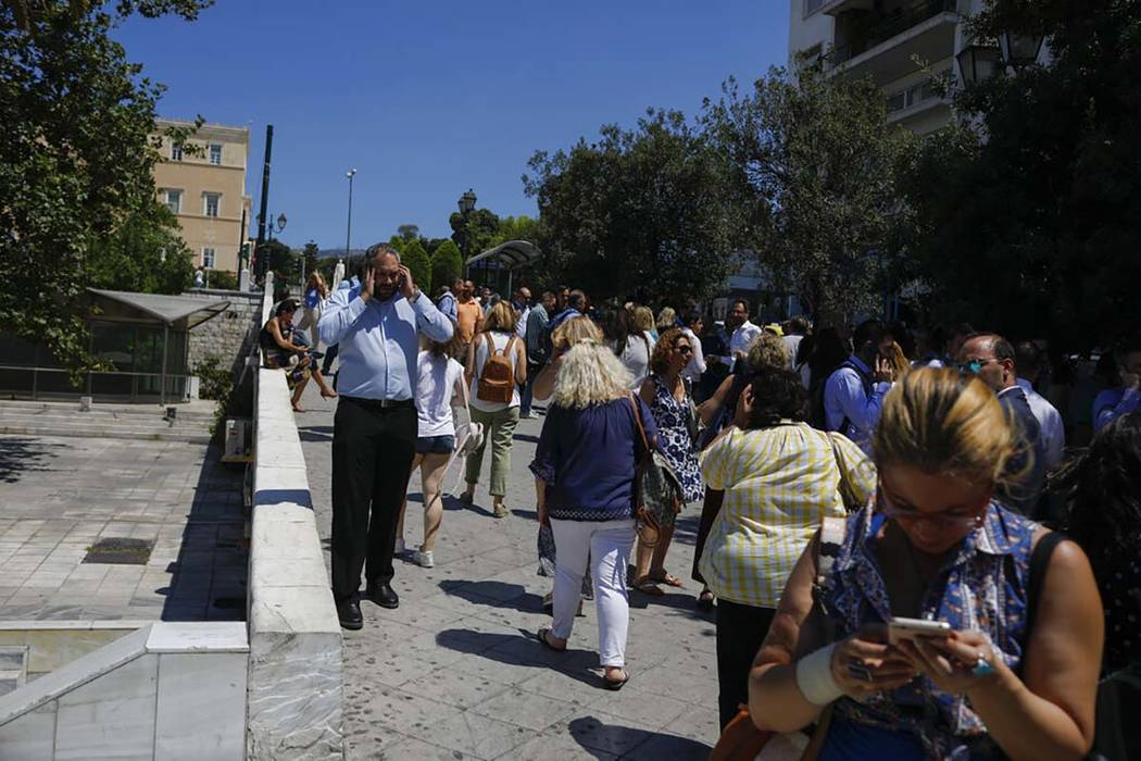 People speak on their phones as they stand outside the building they work in, after a strong ea ...