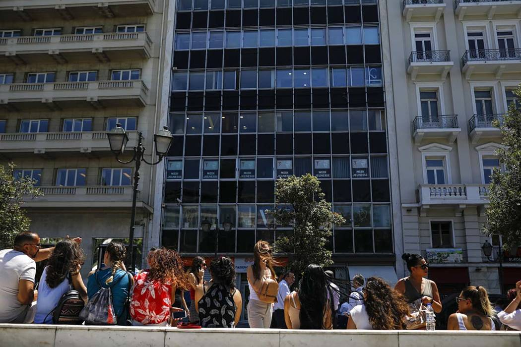 People speak on their phones as they stand outside the building they work in with the Greek Par ...