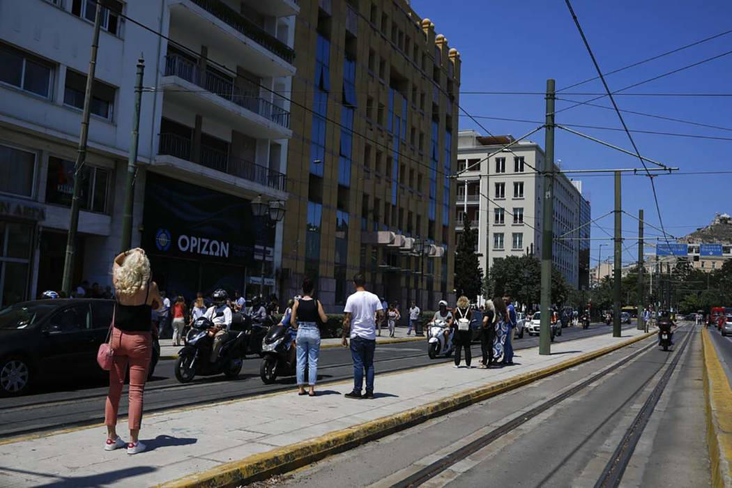 People stand outside the building they work in after a strong earthquake hit near the Greek cap ...