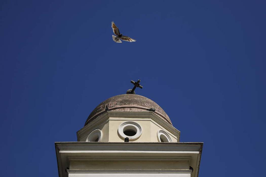 A pigeon flies next the damaged bell tower of Pantanassa church at the Monastiraki square follo ...