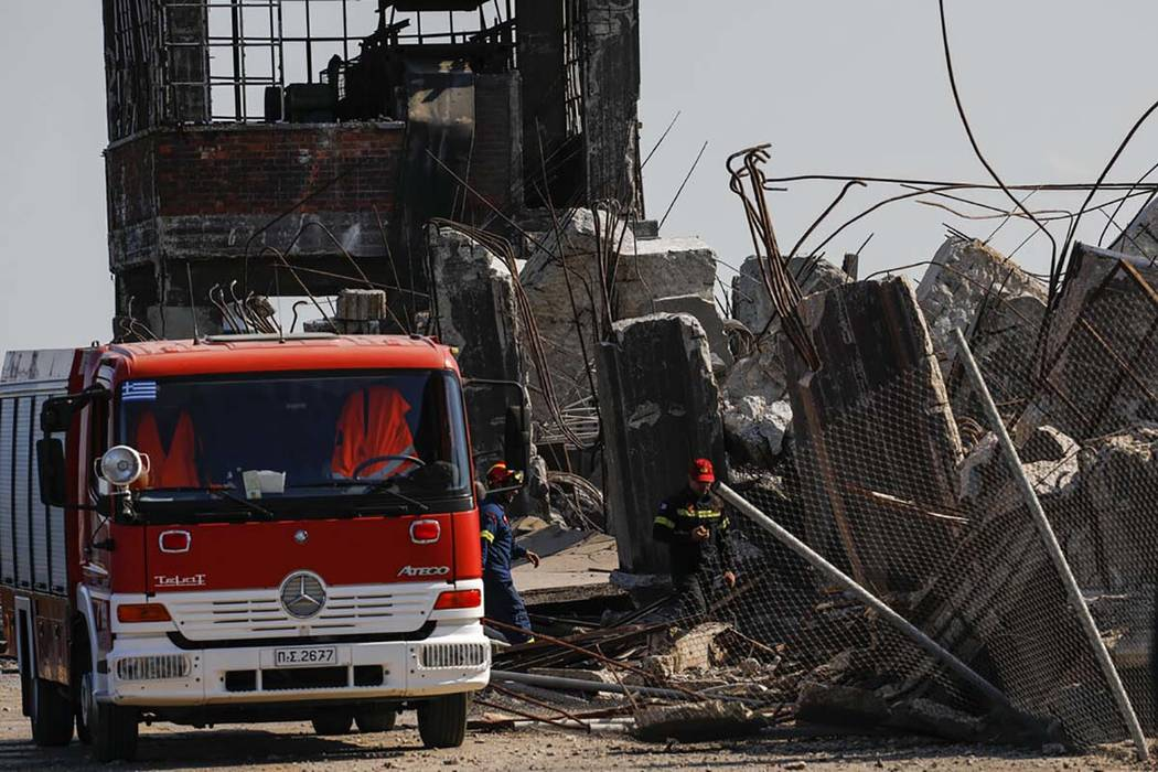 Firefighters search for trapped people at a damaged structure following an earthquake at the po ...