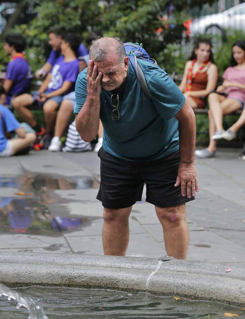 Russ Wilson splashes water on his face from a fountain in New York, Wednesday, July 17, 2019. T ...
