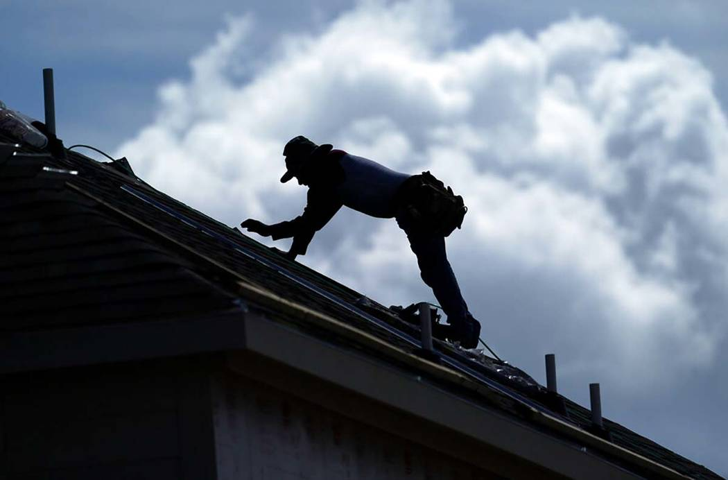 A roofer works on a new home under construction Thursday, July 18, 2019, in Houston. A heat wav ...