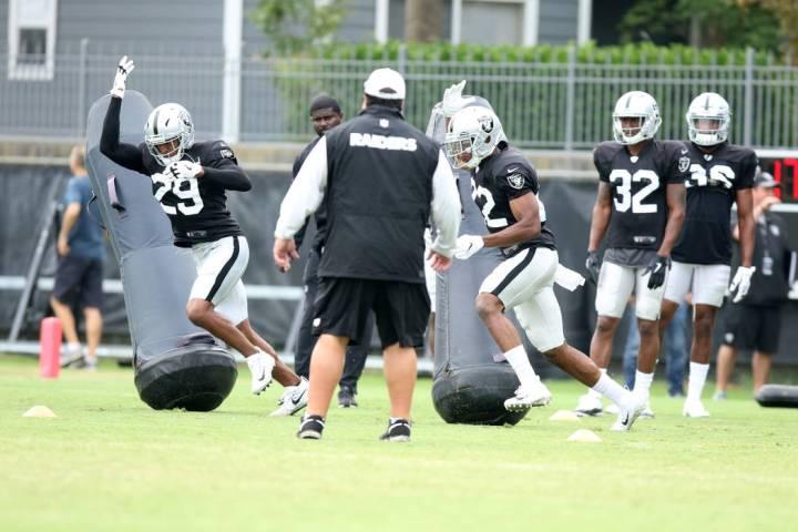 Oakland Raiders defensive backs Leon Hall (29) and Rashaan Melvin (22) brush by tackle posts as ...