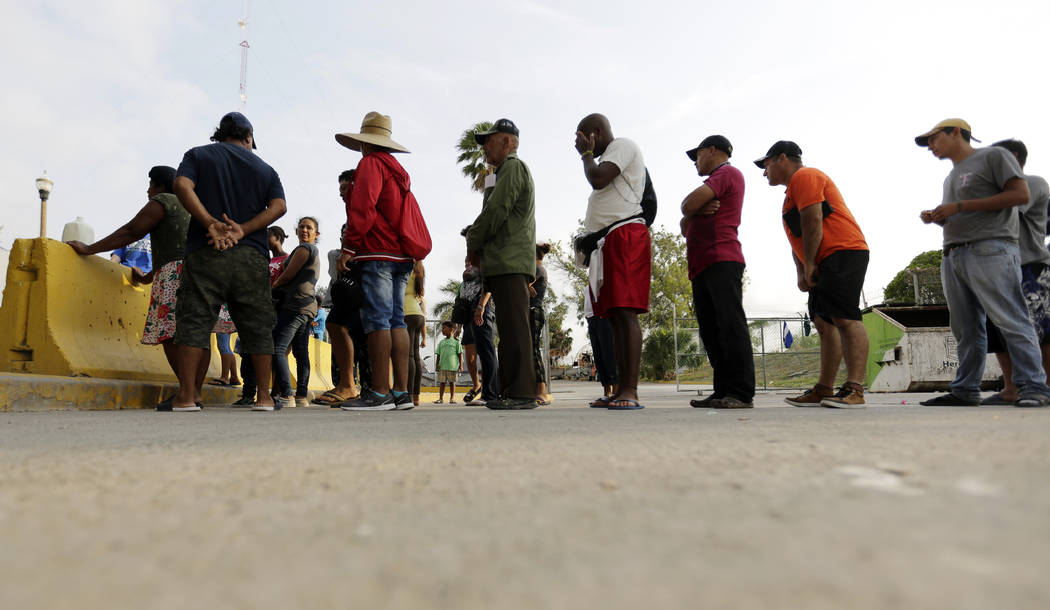 FILE - In this April 30, 2019, file photo, migrants seeking asylum in the United States line up ...