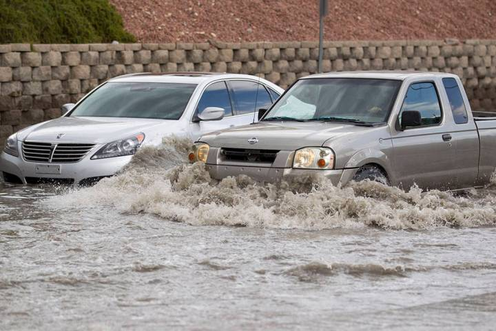 A truck makes its way past a vehicle stalled in floodwaters on West Twain Avenue near Dean Mart ...