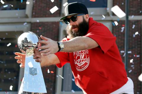 New England Patriots' Julian Edelman reaches for a Super Bowl trophy during their victory parad ...
