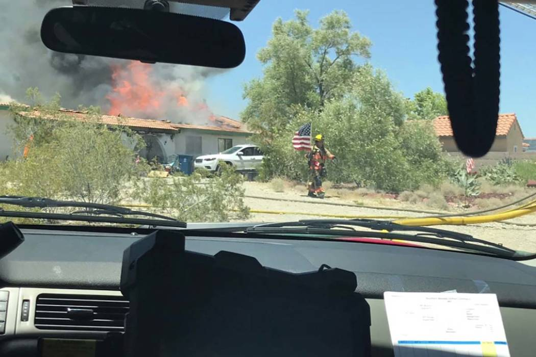 A Las Vegas Fire Department firefighter saves an American flag from a fire on July, 11, 2019. ( ...