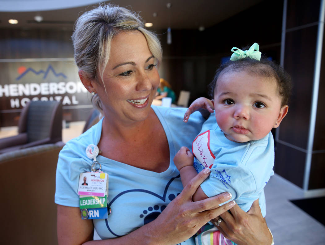 Neonatal Intensive Care Unit Manager Julie Miller holds JudithKaye Montgomery, 6 months, during ...