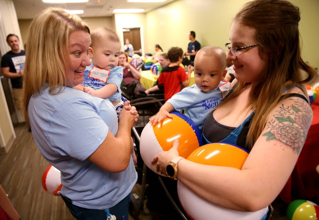 Occupational Therapist Chris Gutierrez, left, with Hunter Graves, 9 months, greets Emily Le and ...