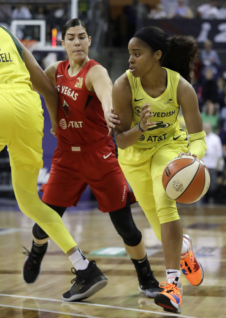 Seattle Storm's Jordin Canada, right, drives past Las Vegas Aces' Kelsey Plum during the first ...