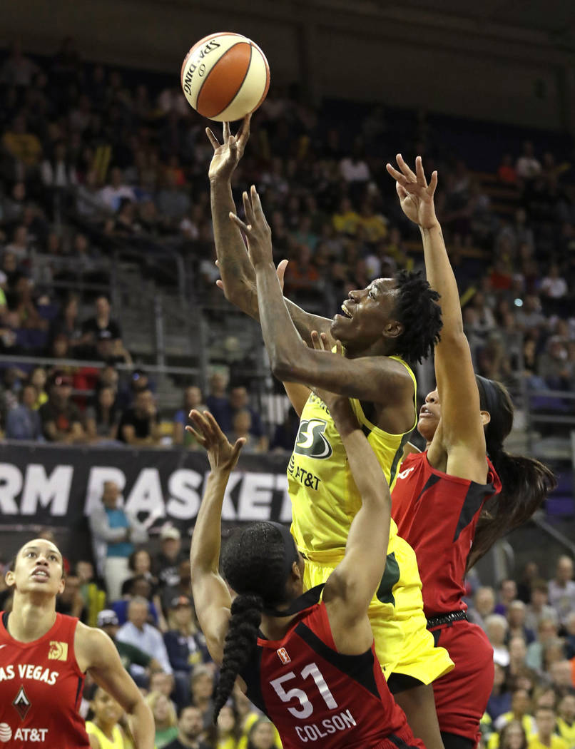 Seattle Storm's Natasha Howard, center, is fouled by Las Vegas Aces' Sydney Colson (51) as Aces ...