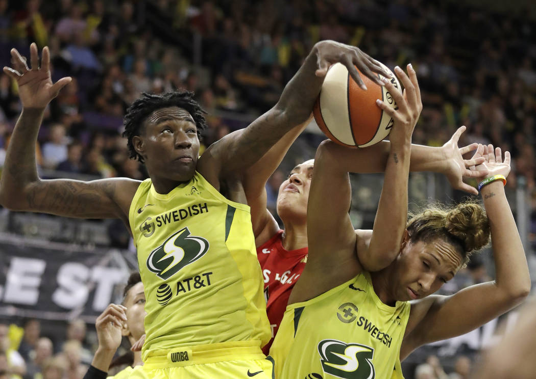 Seattle Storm's Natasha Howard, left, and Mercedes Russell, right, compete for a loose ball wit ...