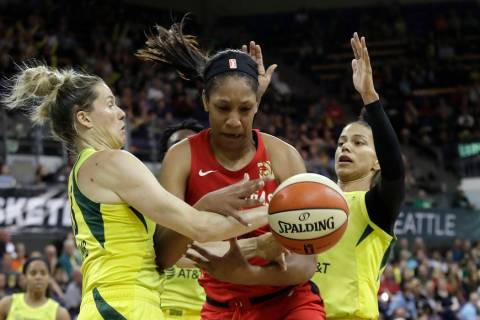 Las Vegas Aces' A'ja Wilson, center, fights for a loose ball with Seattle Storm's Sami Whitcomb ...
