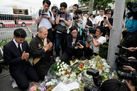 Japanese Diet member, Kenta Izumi, left, and Buddhist monk, Matsumoto Genkun, pay respects at a ...