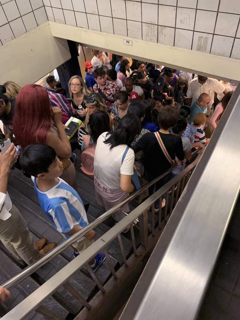 Commuters fill the stairs and line the platform at a New York City subway station as train serv ...