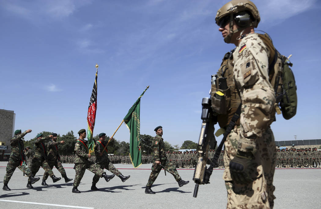 A NATO forces stands guard during the graduation ceremony of newly Afghan National Army soldier ...