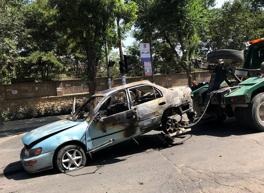 A damaged car is towed away from the site of an explosion in Kabul, Afghanistan, Friday, July 1 ...