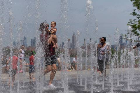 People enjoy the day playing in a water fountain as the Empire State Building is seen from Will ...