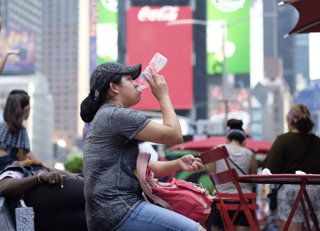 A woman drinks water in Times Square as temperatures reach the mid-to-upper 90s Saturday, July ...