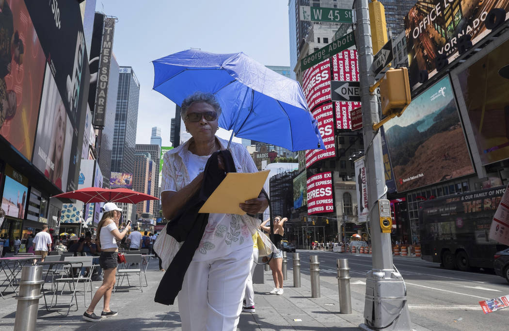A woman uses an umbrella to block out the sun while walking through Times Square, Saturday, Jul ...