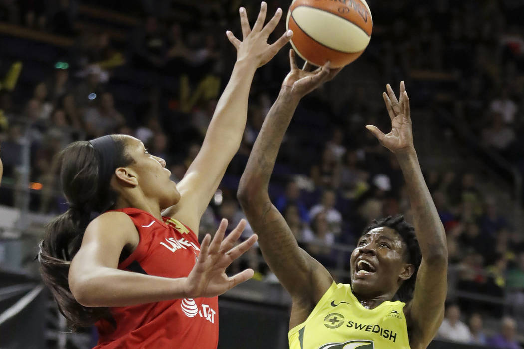 Seattle Storm's Natasha Howard, right, shoots as Las Vegas Aces' A'ja Wilson defends during the ...
