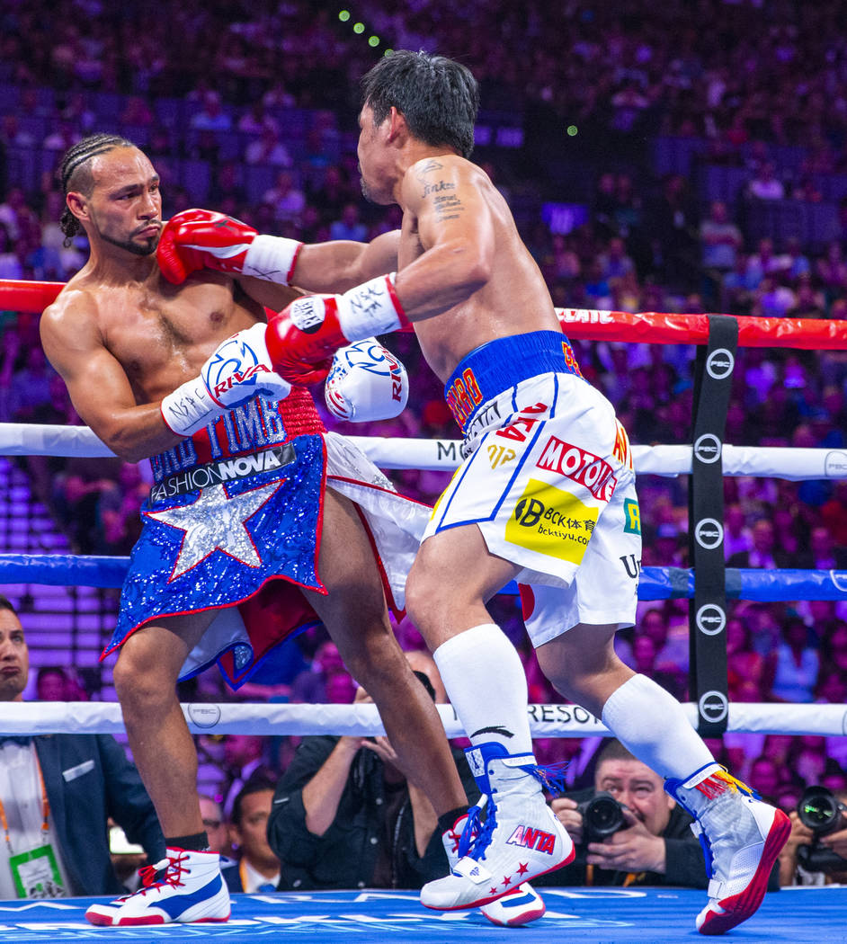Keith Thurman is punches in the face by Manny Pacquiao during Round 2 of their WBA super welter ...