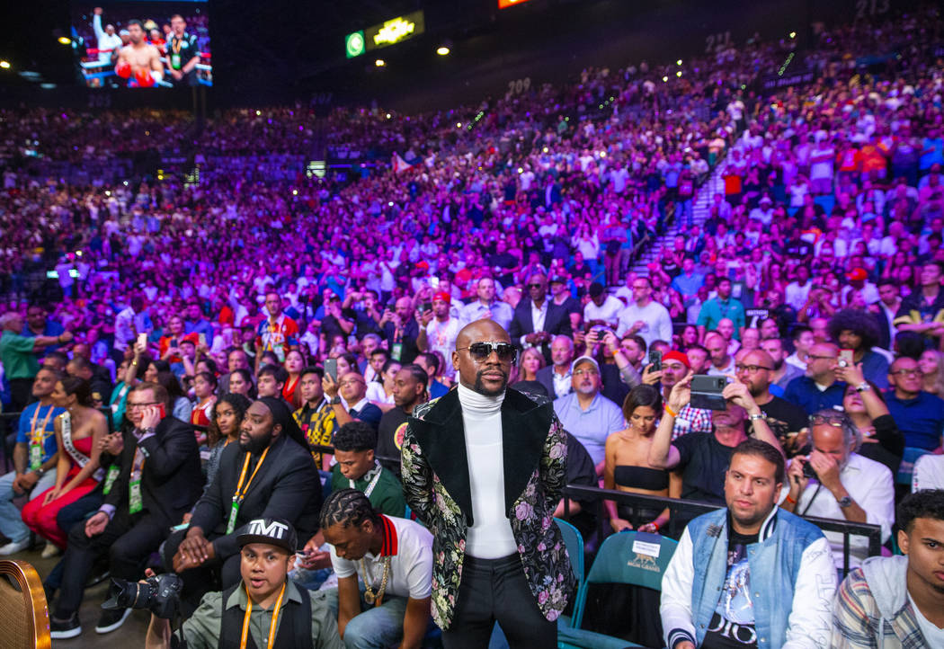 Former boxer Floyd Mayweather Jr. watches as Manny Pacquiao and Keith Thurman enter the ring du ...