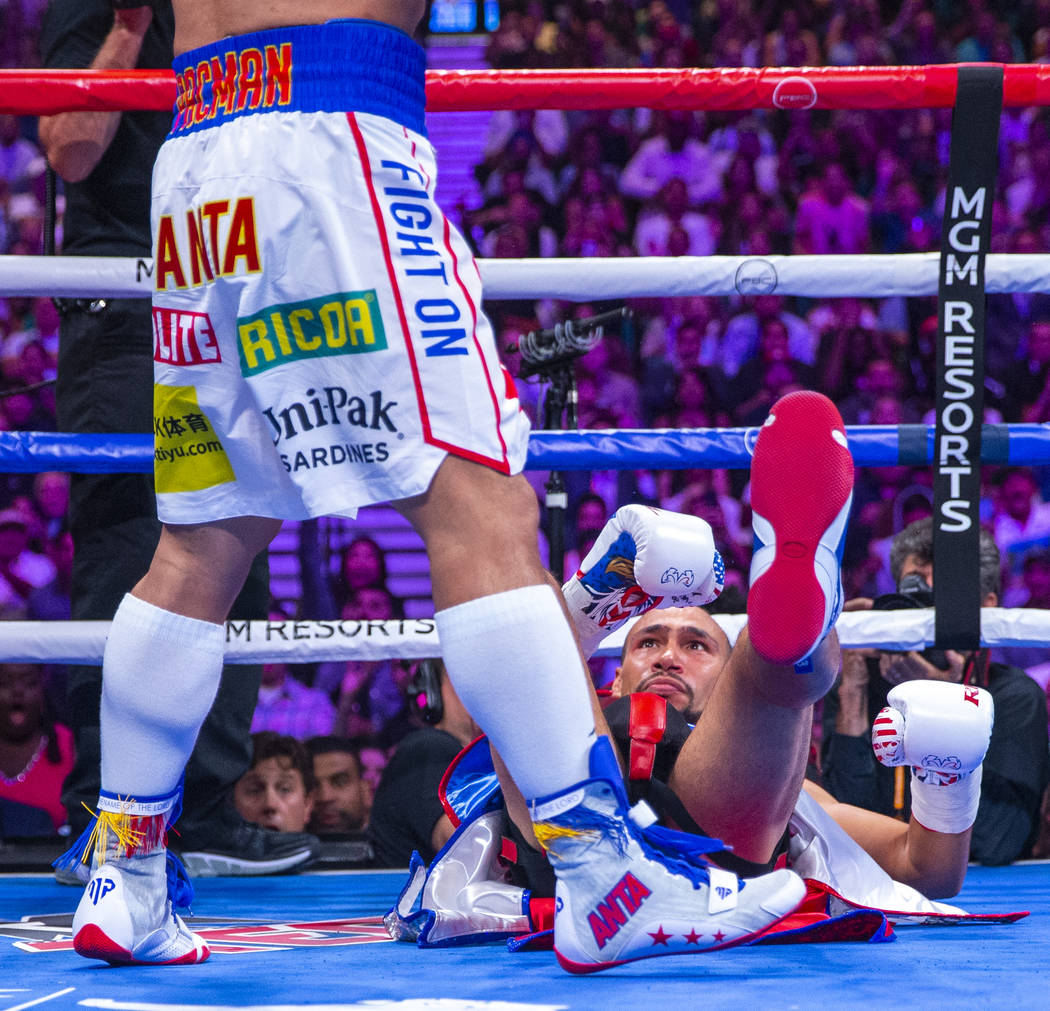 Manny Pacquiao, left, stands over Keith Thurman who went down in Round 1 during their WBA super ...