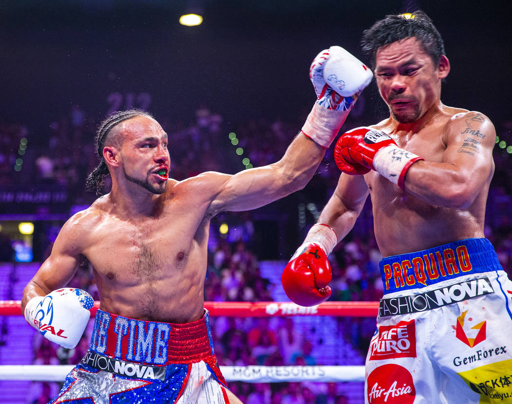 Keith Thurman, left, connects with a shot to the face of Manny Pacquiao during Round 6 of their ...