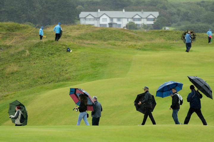 Spectators hold umbrellas as they cross the 15th hole in the rain as golfers practice ahead of ...