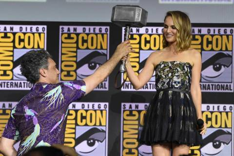 "Director Taika Waititi hands the Thor hammer to Natalie Portman during the ""Thor Love And ..."