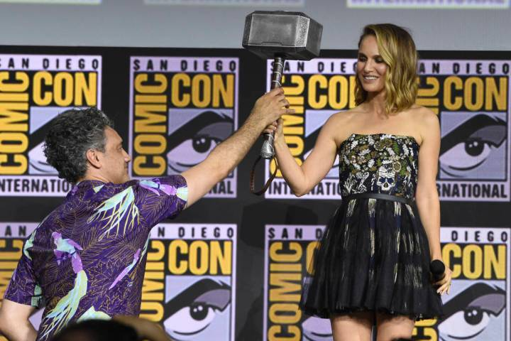"""Director Taika Waititi hands the Thor hammer to Natalie Portman during the """"Thor Love And ..."""