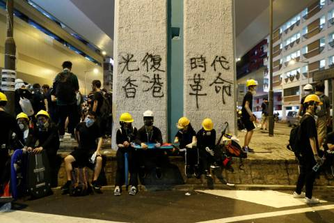 "Protesters rest near graffiti which reads ""Recovery of Hong Kong, An Era Revolution"" ..."