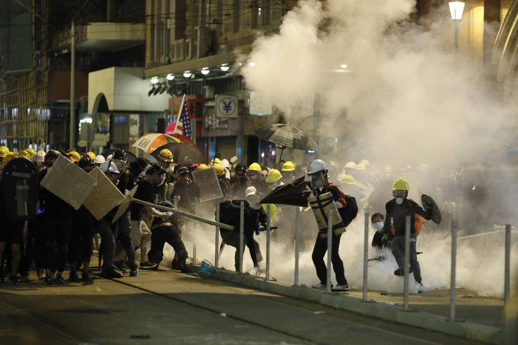 Protesters react to teargas as they confront riot police officers in Hong Kong on Sunday, July ...