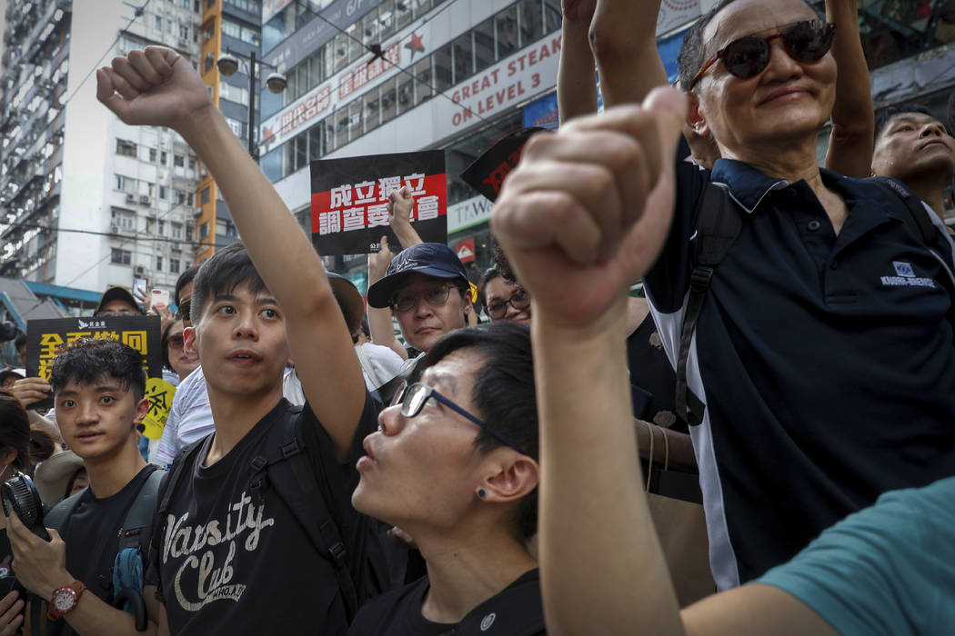 Protesters gestures during a march on a street in Hong Kong, Sunday, July 21, 2019. Thousands o ...